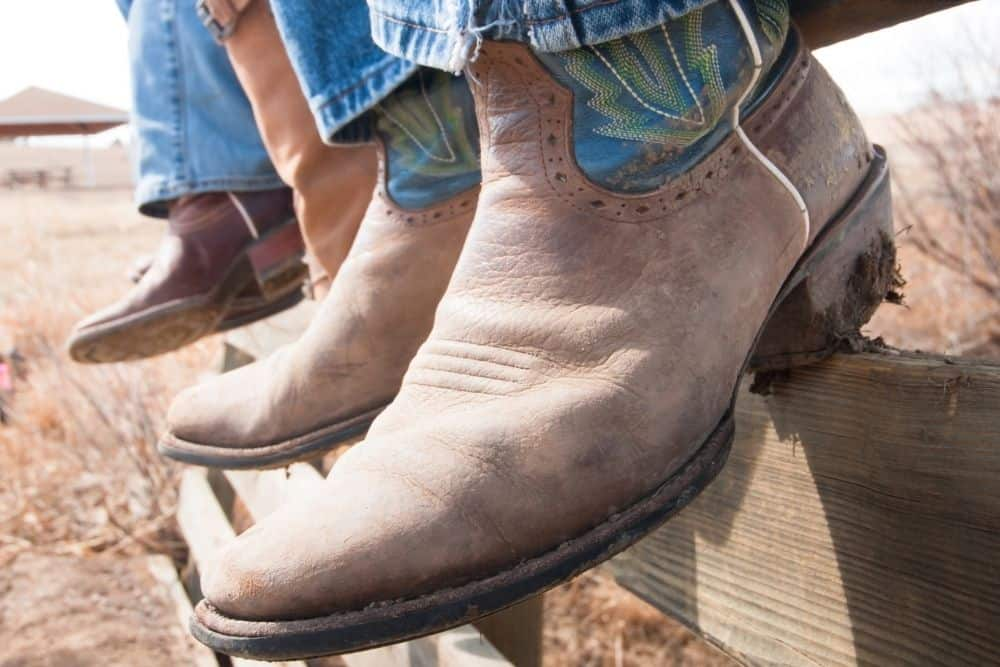 men wear cowboy boots sit on the fence