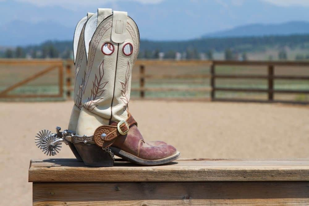 cowboy boots with riding heel on the wood table in the farm