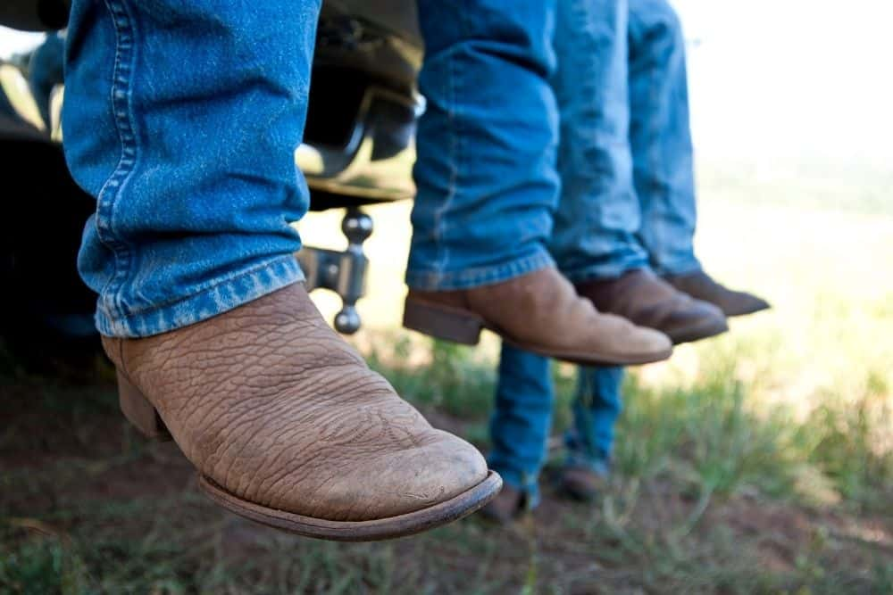 Mens wear cowboy boots and sit