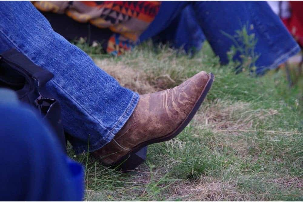 What jeans look good with cowboy boots? When wearing cowboy boots with jeans, men don't tuck jeans into cowboy boots, they do the opposite. For matching with men's cowboy boots, the end of jeans must be wide enough to fit the boot shaft. Bootcut jeans are an extremely suitable partner to pair with cowboy boots. It is no exaggeration to say that they are God's gift to cowboy boots. Bootcut jeans can make a nice cowboy look because they fit neatly from the knees upwards, and they get wider from knees to the end – enough to tuck the shaft into cowboy boots. This is the standard to choose suitable jeans to wear with cowboy boots!