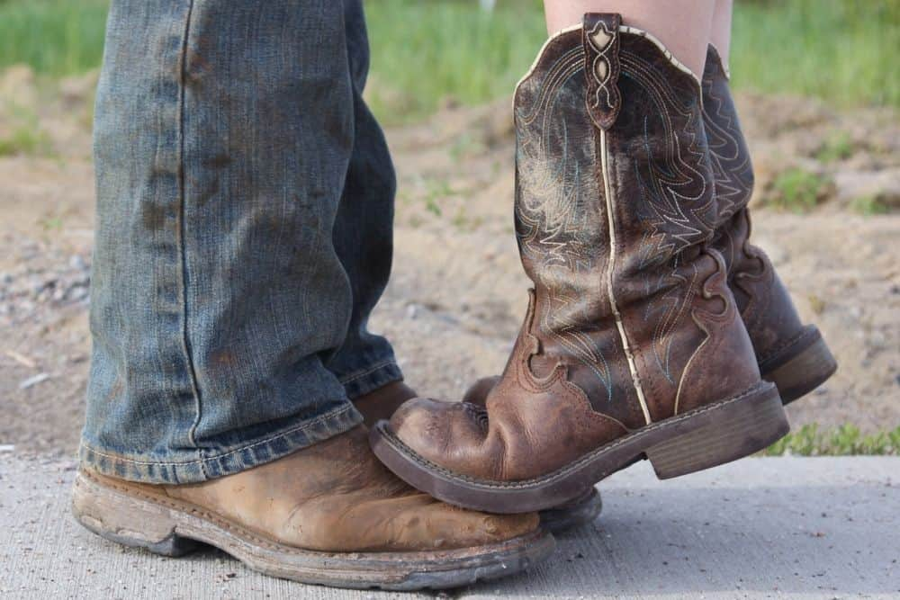 Women wearing cowboy boots stands on the feet of another man wearing cowboy boots