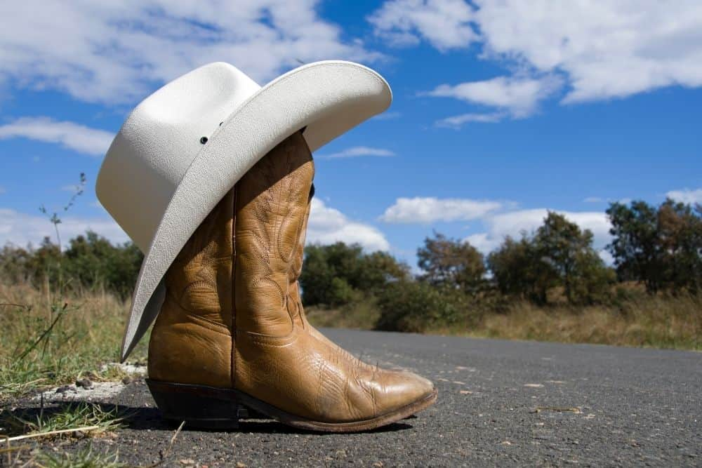 cowboy boots and cowboy hat on the road