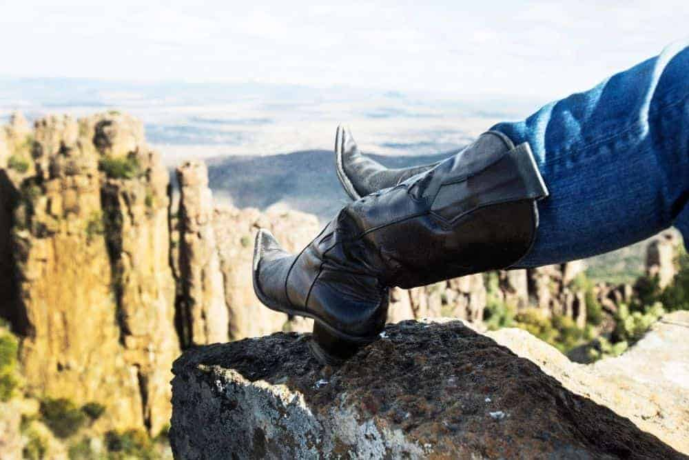 wearing jeans with black pointed toe cowboy boots hiking on rocky mountain