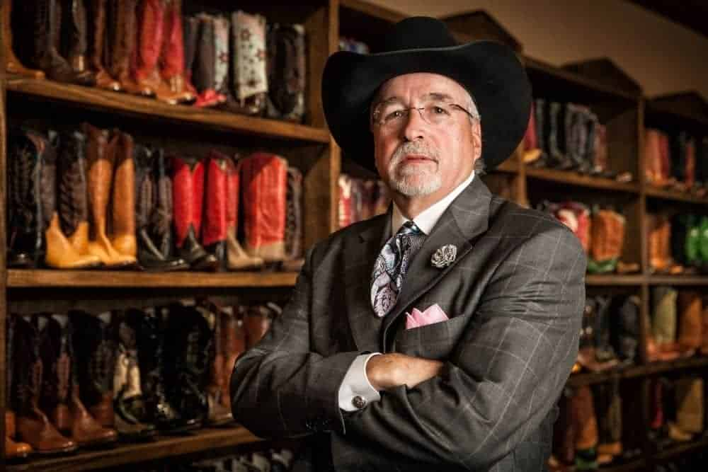 an old business man wearing a cowboy hat and suit standing ahead of a big cowboy boot shelf