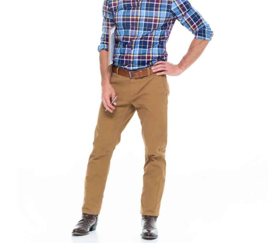 man wearing a checkered dress shirt, khakis pants with cowboy boots for a formal look