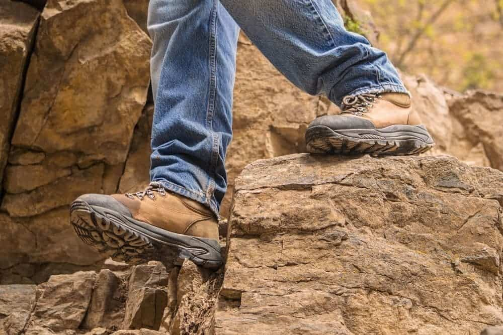 One man wear hiking boots to hike in the rocky terrain