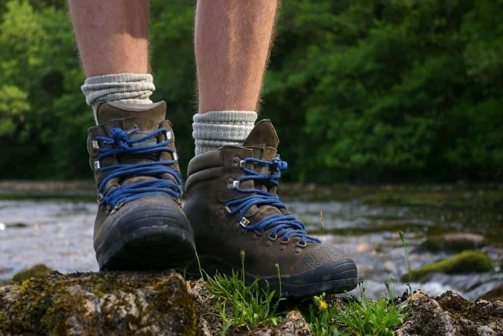One men wear hiking boots stand on the rock