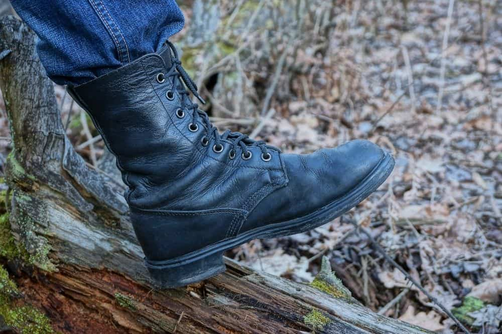 One man wear tactical boots stand on the wood