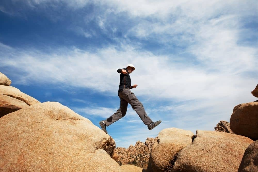 man with hiking boots jumps on rocks in Joshua Tree nation park