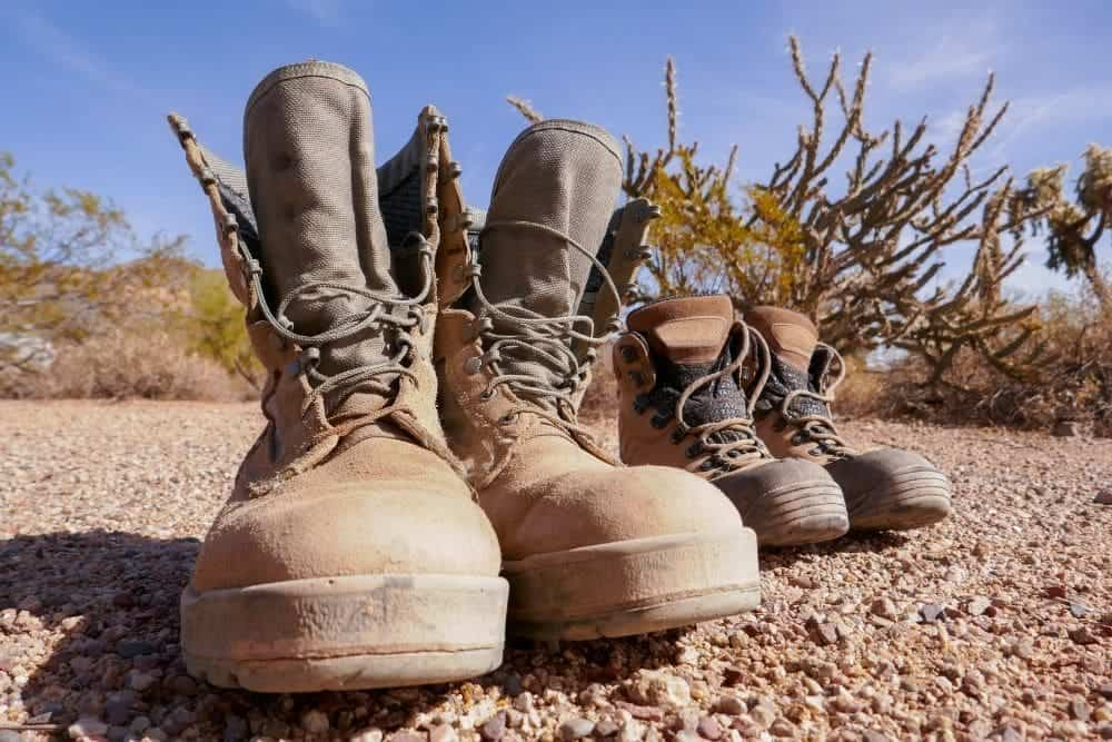 2 pair of hiking boots on the road under the sun