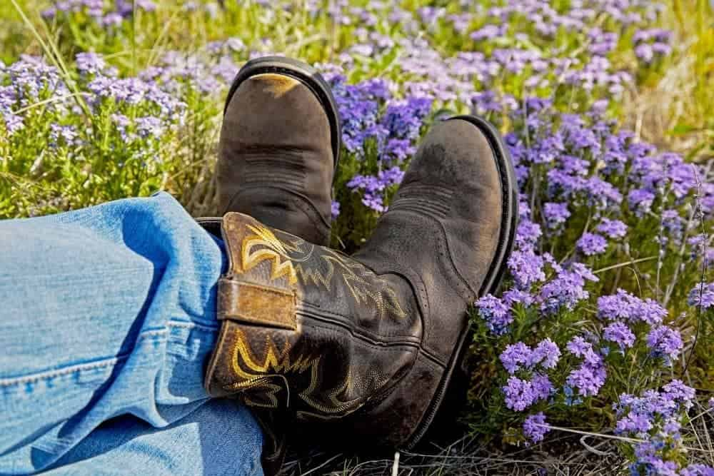 a person wearing jeans and cowboy boots sitting on flower field