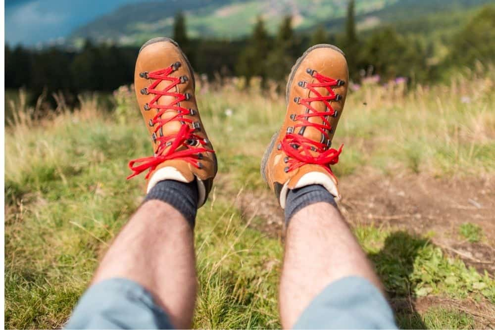 man wear orange hiking boots that have red laces
