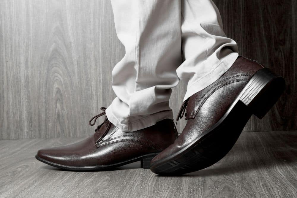 man wearing brown glossy fashionable dress shoes