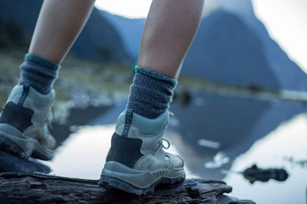 man wearing gray socks with hiking boots standing near a lake