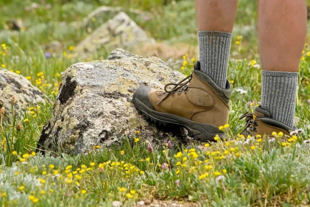 man wearing gray tall socks with hiking boots