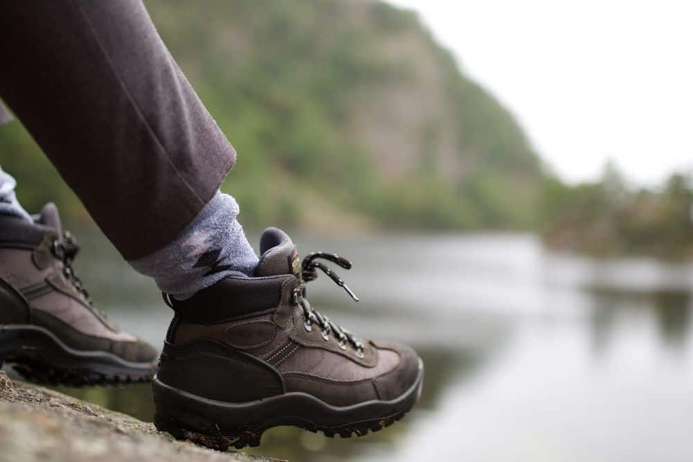 man wearing hiking boots to stretch them