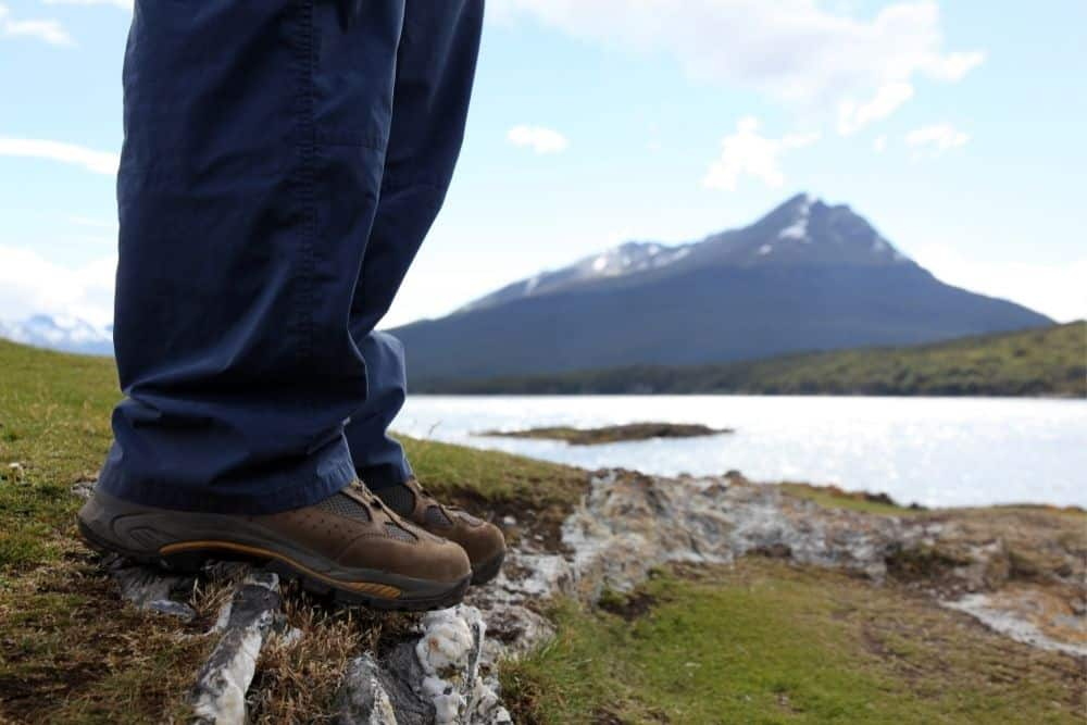 man wearing jeans and hiking boots standing near the lake and mountain