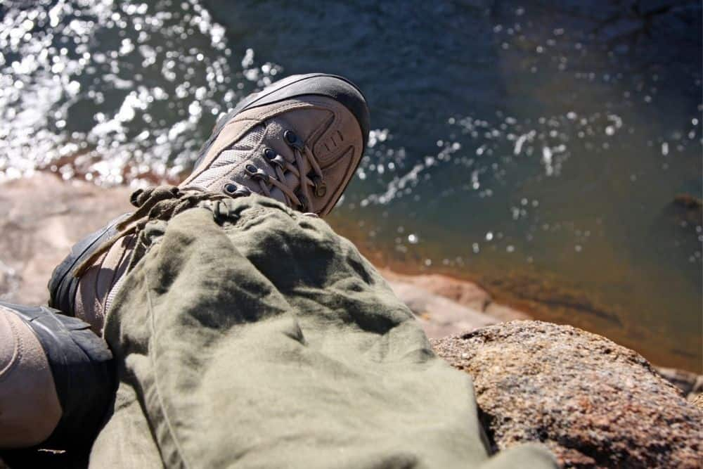 man wearing right size of steel toe hiking boots sitting near a lake