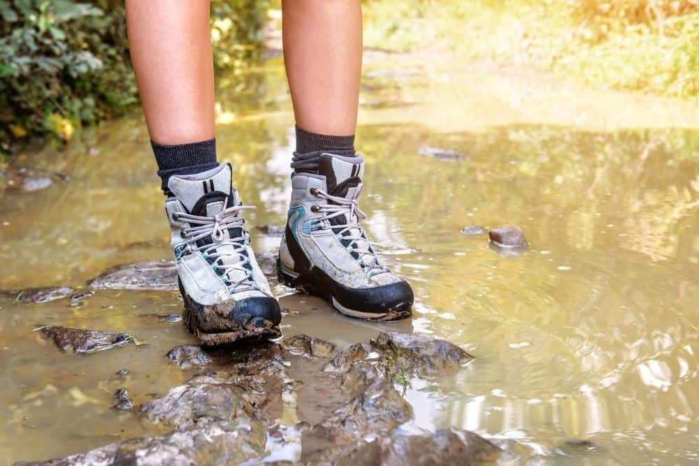women wear hiking boots stand on the muddy and wetness place