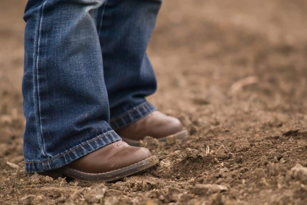 kid wear cowboy boots stand on the muddy ground