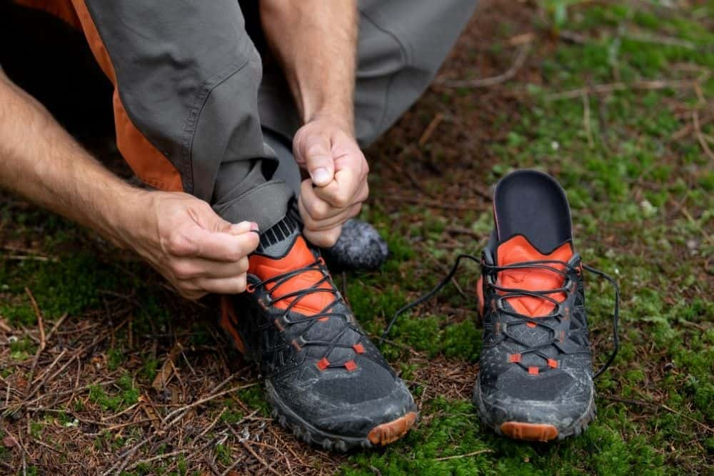 man changes the insole of hiking boots