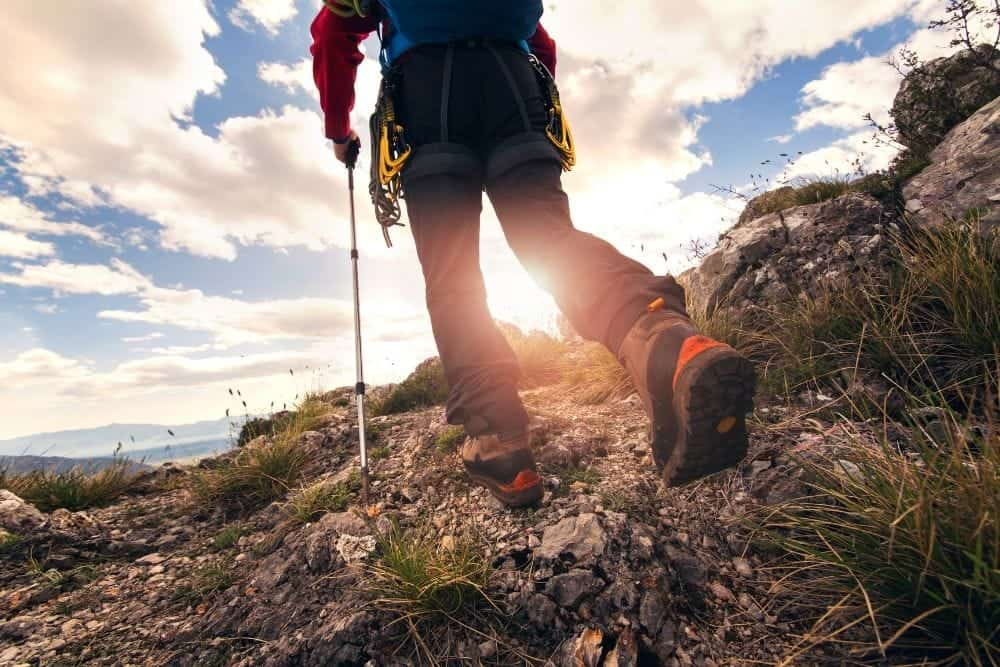man wearing hiking boots on rugged outdoor terrain