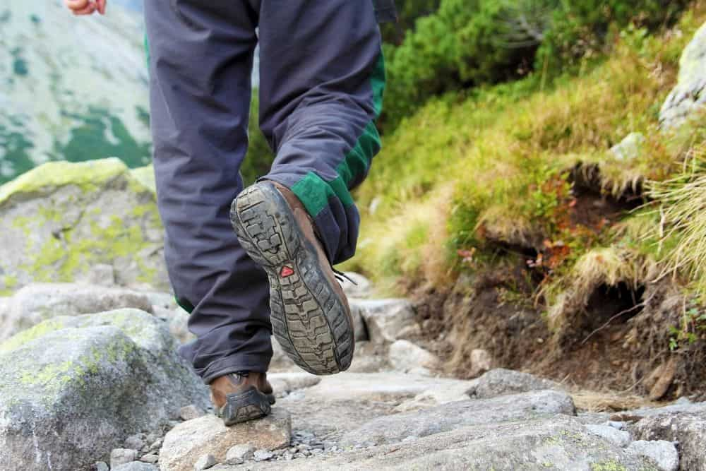 man wearing hiking boots with heel for shock absorption on rough terrain