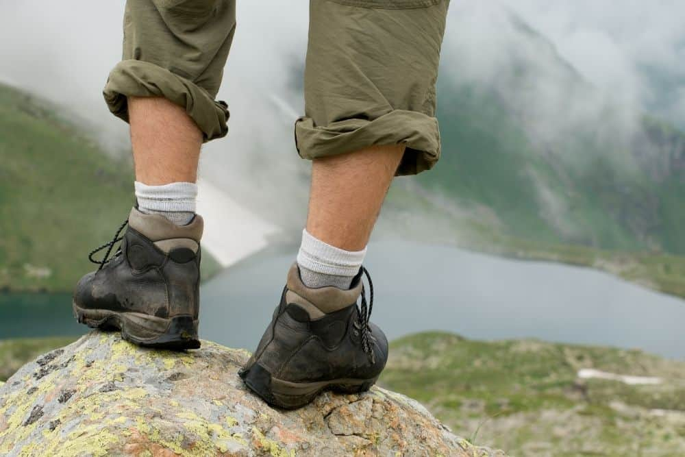 man wearing hiking boots with heels standing a rock