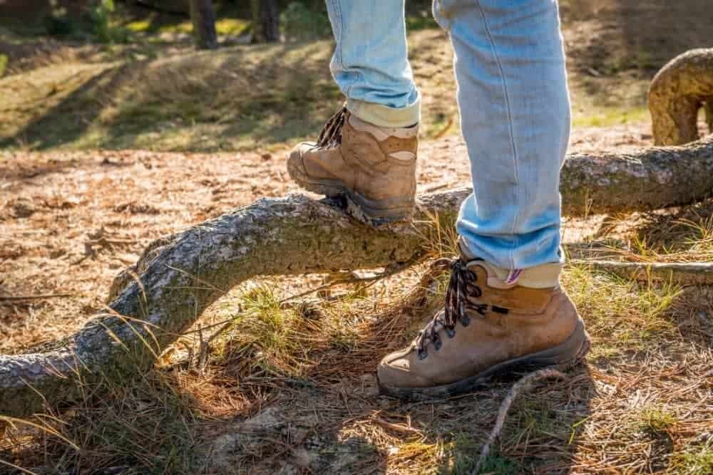 man wearing hiking boots with heels standing on a fallen branch