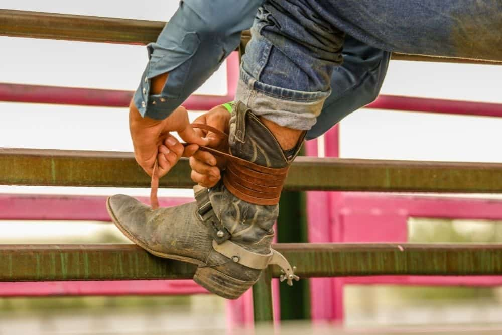 men tighten his cowboy boots with a leather lace