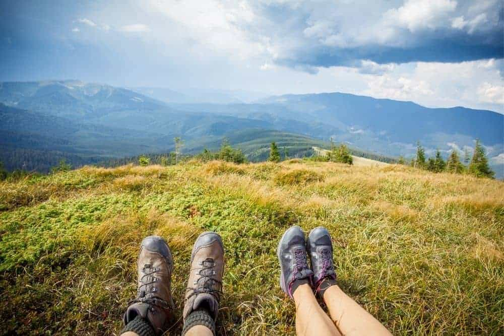 two people wearing broken in hiking boots sitting on a mountain